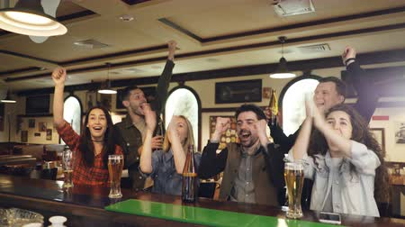 támogató : Friends football fans are cheering on in sports bar watching important match and having fun in the end. They are clinking glasses and drinking beer. Stock mozgókép