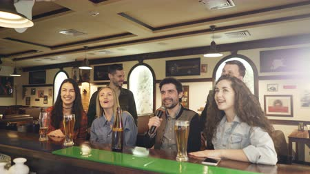 караоке : Young cheerful friends are singing together in karaoke bar while sitting at counter and having fun. They are laughing, dancing and gesturing enjoying night out.