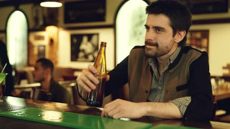 меланхолия : Handsome young man is drinking beer sitting alone at bar counter. Bearded guy in casual clothing is upset. Customers having fun in background.