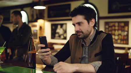 общаться : Young male student is using smart phone sitting in fancy bar with bottle of beer. He is touching screen and smiling. Modern ways of communication concept.