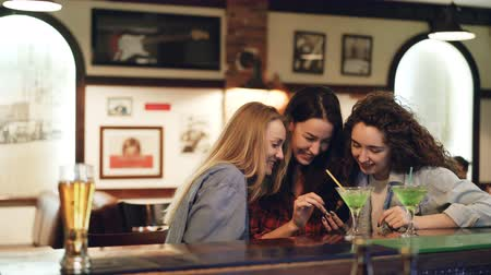 socializing : Girls are using smartphone, laughing and talking while sitting in bar together. Girls in casual clothing are watching screen and chatting. Modern technologies for fun concept. Stock Footage