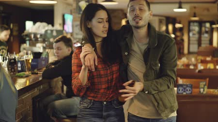 namorado : Dolly shot of young woman helping her drunk boyfriend leave bar. Handsome bearded man is holding beer bottle and telling something to his girlfriend. Vídeos