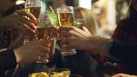 snack : Close-up shot of male and female hands holding beer and cocktail glasses and clinking them. Faces of young men and women in background, focus on glasses.