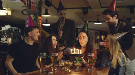 паб : Young pretty brunette is making wish and blowing out candles on birthday cake while celebrating birthday in cafe with friends. Happy people in party hats are clapping hands