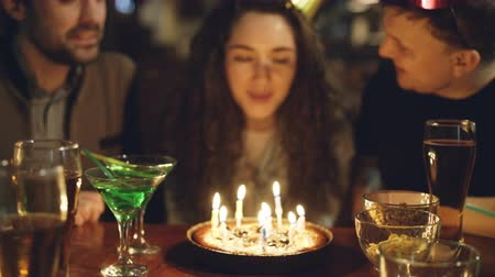 make friends : Close-up shot of young pretty woman blowing out candles on birthday cake. Happy people are laughing and clapping hands.