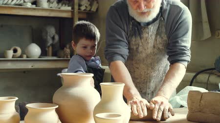 oleiro : Experienced male potter is mixing and kneading clay while his cute young grandson is helping him in workshop. Pottery, family tradition and childhood concept. Stock Footage
