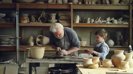 oleiro : Professional male potter is working with clay on spinning throwing-wheel with his curious grandson helping him. Ceramic pots, vases and figures are visible.