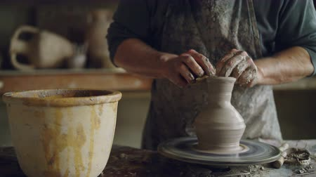 concentrar : Elderly craftsman is creating ceramic jar on potters wheel using professional tools. Workplace with handmade pots, beautiful vases and figures in background.