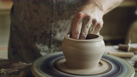 conventional : Close-up shot of half-finished ceramic pot spinning on throwing wheel and hands cutting clay with professional tools. Creating eathenware and traditional pottery concept. Stock Footage