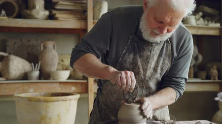 conventional : Senior ceramist is smoothing bottom of half-finished of ceramic pot on spinning potters wheel in workplace. Creating traditional eathenware and conventional pottery concept.