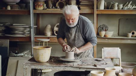 conventional : Senior man professional potter is making bowl from clay on spinning potters wheel, broadening and smoothing wet clayware. Different handmade ceramic figures in background.