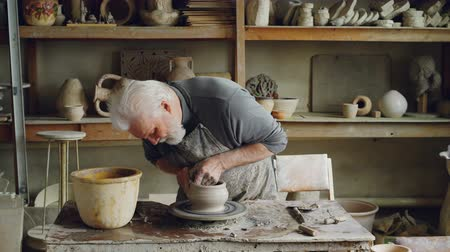 se zaměřením : Skilled elderly potter is producing ceramic pot on turning wheel in workplace. Creation process, traditional pottery and interesting hobby concept. Dostupné videozáznamy
