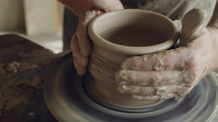 ügyesség : Close-up shot of male hands working with clay on spinning potters throwing wheel, decorating pot, making ornament. Pottery, hobby and handicraft concept.