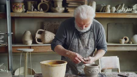 conventional : Experienced craftsman is making ear for ceramic bowl and fixing it on clayware while working in cozy workplace. Pottery, profession and hobby concept.
