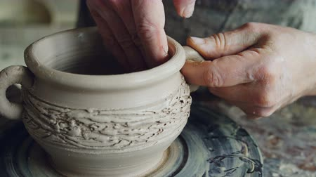 conventional : Close-up shot of muddy male potters hands shaping and fixing ears of ceramic bowl. Nimble craftsman is forming clay professionally creating beautiful clayware.