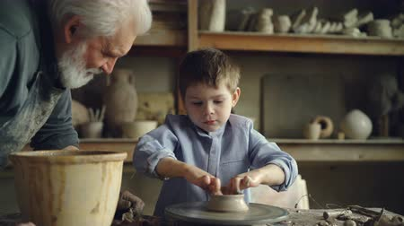 стартер : Little boy pottery learner is creating clayware on throwing-wheel while his experienced grandgather is talking to him and helping him. Making ceramics and family concept.