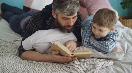 stories : Loving parent bearded man is reading interesting book to his curious little son on double bed at home. Parenthood, happy people, love and family concept.