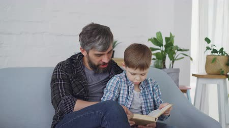 paternal : Caring father is teaching his little son curious preschooler to read. They are sitting together on sofa and reading book aloud wearing casual clothes.