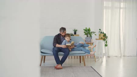 paternal : Bearded man is reading book and showing illustrations to his son while relaxing on sofa in light apartment. United family, spending leisure time and raising children concept. Stock Footage