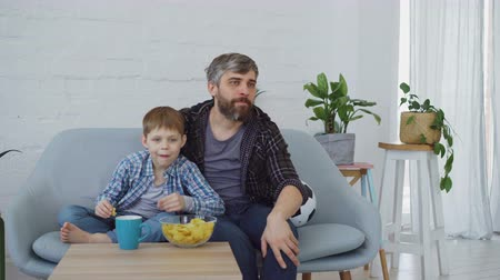 penas : Football fans bearded man and his little child are watching match on TV at home, celebratong goal and eating crisps. Spending time with family and sport concept. Stock Footage