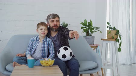 концентрированный : Family members father and son are watching soccer match on TV at home, cheering, celebrating victory and eating snacks. Happy family and sport concept.