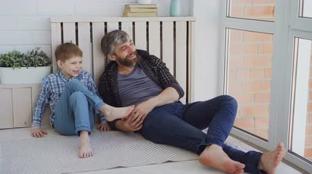 paternal : Cheerful handsome man is looking out of large window with his little son, pointing outside and talking. Friendly conversation, happy family and bonding concept. Stock Footage