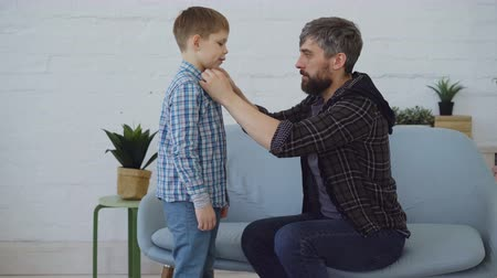helpful : Careful father is helping his little son to get dressed, buttoning his shirt and smooting hair. Loving parent, happy childhood and paternal attention concept.