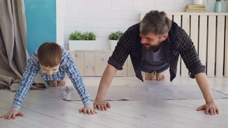 сильный : Active handsome father and his joyful son are exercising doing press-up together at home on wooden floor. Happy family, sport and sporty lifestyle concept.