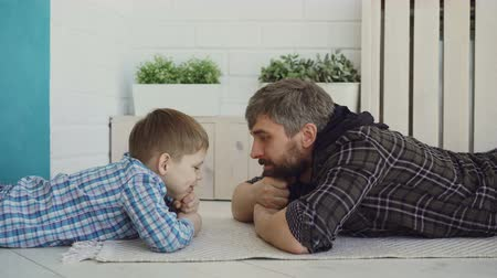 paternal : Cute small child is lying on floor with his loving dad, looking at him and talking. Happy family, interesting conversation, childhood and parenthood concept.