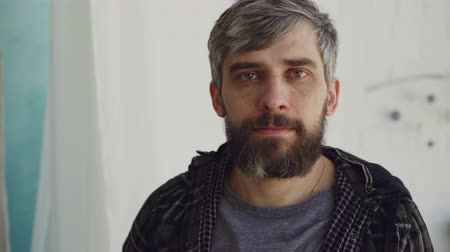 encanecido : Close-up portrait of handsome bearded man with brown eyes and grayish hair wearing casual clothes and looking at camera. People and interior concept.