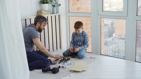 alicate : urious little son and loving father are busy with woodwork working with instruments and driving nails with hammer. Fatherhood and construction concept