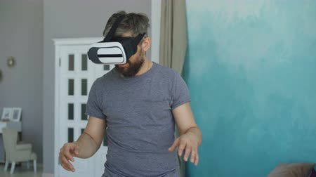 entertain : Bearded man in casual clothes is using virtual reality glasses and gesturing while standing in his apartment. Modern technology, entertainment and people concept.