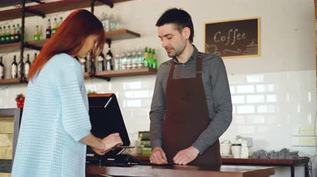 payment terminal : Attractive young woman is talking to friendly male cashier, paying for takeaway coffee with mobile phone at coffee shop, then taking glass and leaving.
