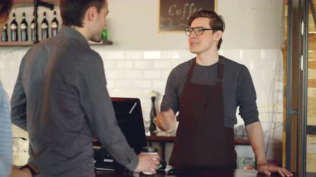 payment terminal : Friendly barista handsome man is selling takeout coffee and accepting contactless mobile payment with smart phone. Modern technolofy, coffee shop and banking concept. Stock Footage