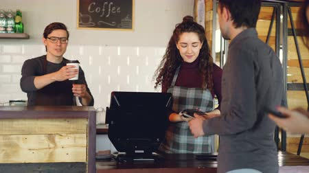 garçonete : Attractive woman talkative cashier is accepting contactless payments with mobile phone and talking to customers and friendly waiter in apron is bringing takeaway coffee.