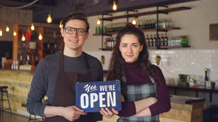 официант : Cheerful attractive people coffee-house owners are holding we are open sign while standing inside coffee shop. Opening new business and people concept.