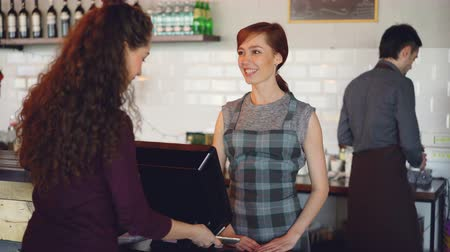 официант : Cheerful workers of coffeehouse are greeting customers, taking payments with smartphone using bank cards terminal and selling takeaway drinks to young people.