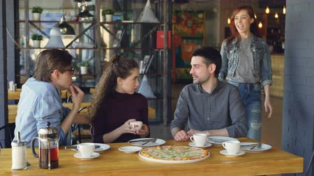 brim : Pretty young girl is meeting her friends in pizza house doing high five and talking to mates drinking tea. Friendship, modern lifestyle and eating out concept.