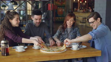 pozitivity : Close friends young men and women are sharing large pizza eating delicious food in cozy cafe and talking. Friendship, eating out and communication concept. Dostupné videozáznamy