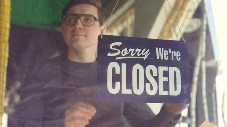 invite : Attractive male waiter in apron is changing doorplate from sorry we are closed to yes we are open. Beginning new work day, employee and business concept. Stock Footage