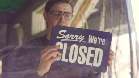 diner : Busy cafeteria waiter in apron is looking outside through glass door and changing doorplate from sorry we are closed to yes we are open. Starting work day and business concept. Stock Footage