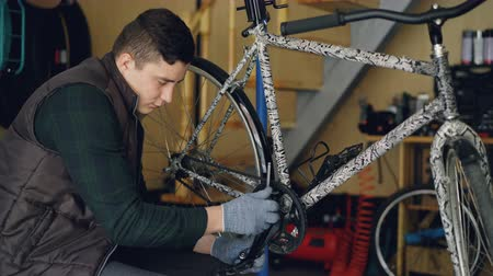 treadle : Skilled young man professional mechanic is fixing bike treadle with key sitting near bicycle on floor of his workplace. Maintenance, tools and people concept. Stock Footage