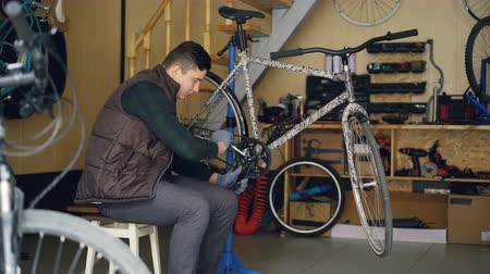 фиксировать : Experienced master is repairing bicycle treadle with special tools key wrench while working in workshop with spare parts and equipment. People and maintenance concept. Стоковые видеозаписи