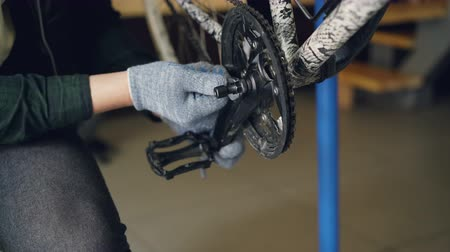 затянуть : Close-up shot of male hands in protective gloves repairing broken bicycle treadle with wrench in workshop. Profession, people and maintenance concept.