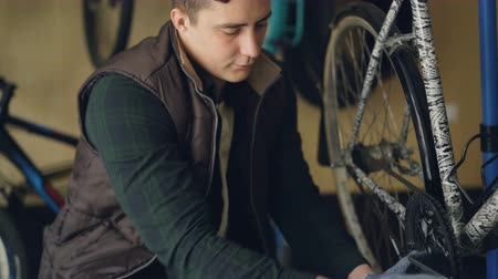 treadle : Young bicycle repairer is fixing bike treadle mechanism using special key. Man is concentrated on his work, he is wearing protective gloves and warm vest uniform.