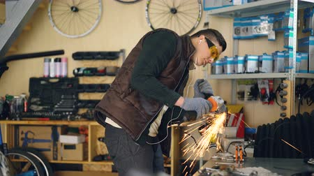 repairer : Maintenance man is using electric circular saw while working in his small workplace. Young man is wearing protective glasses and gloves and is listening to music with earphones. Stock Footage