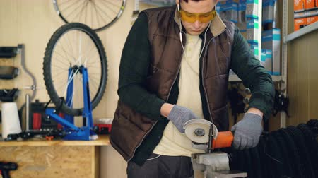 óculos de proteção : Tilt-up shot of mechanic working with electric circular saw fixing small metal part. Shielding spectacles and protective gloves, bicycle spare parts and tools are visible.