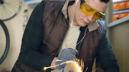 velo : Serious repairman in safety goggles is using electric circular saw while sawing metal bicycle spare part in workplace. Bright sparks are in foreground. Vídeos