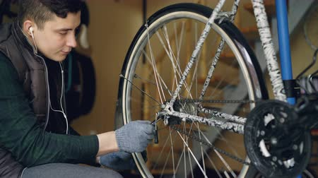 treadle : Young bike repairing master is adjusting wheel mechanism with wrench and rotating wheel to check quality of work. Cycle maintenance and working people concept.