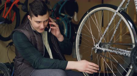 sobressalente : Cheerful maintenance man is talking on mobile phone while working in bike rapair workshop checking wheel spokes and turning wheel. Repairing and communication concept. Vídeos